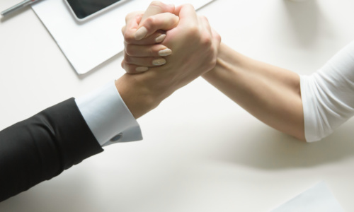 Businessman and businesswoman gripping each others hand, competing in arm wrestling, trying to pin the others arm on office desk. Close up of arms. Rivalry, competitive market. Business concept photo